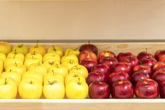 Maçãs amarelas e vermelhas frescas na prateleira na loja foto de stock