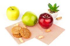 Maçãs, amendoins e cookies de farinha de aveia em uma tabela branca Fotografia de Stock