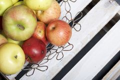 Maçãs aromáticas maduras em uma cesta de aço Localizado em uma caixa de madeira, batida fora das placas fotos de stock royalty free