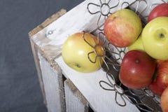 Maçãs aromáticas maduras em uma cesta de aço Localizado em uma caixa de madeira, batida fora das placas imagem de stock