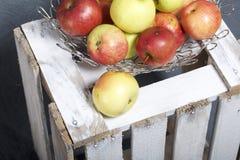 Maçãs aromáticas maduras em uma cesta de aço Localizado em uma caixa de madeira, batida fora das placas foto de stock