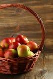 Maçãs bonitas na cesta no fundo de madeira Fotografia de Stock