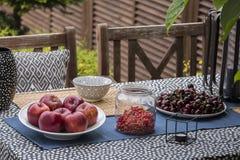 Maçãs, cerejas e corintos na tabela no terraço da casa Foto real imagem de stock