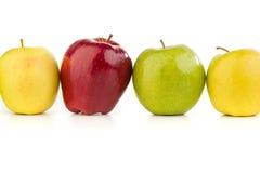 Maçãs coloridos em seguido em uma tabela branca Imagem de Stock