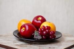 Maçãs com uvas e laranjas fotografia de stock royalty free