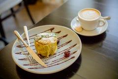 Maçãs cozidas com requeijão, porcas, passas e copo de café Apple com café da arte do latte na tabela Sobremesa do café da manhã foto de stock