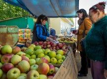 Maçãs da compra das mulheres no mercado do ` do pássaro do ` em Voronezh imagens de stock royalty free