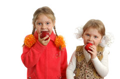 Maçãs da mordida das meninas no branco Foto de Stock