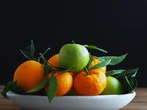 Maçãs da tangerina, as alaranjadas e as verdes na placa branca Frutos orgânicos que estão no assoalho de madeira com folhas fotografia de stock royalty free