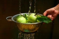 Maçãs de lavagem no escorredor Fotos de Stock Royalty Free