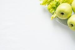 Maçãs e aipo verdes frescos no fundo branco de pano Foto de Stock Royalty Free