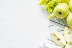 Maçãs e aipo verdes frescos no fundo branco de pano Imagens de Stock