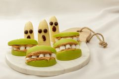 Maçãs e bananas saudáveis dos petiscos de Dia das Bruxas na placa de corte com fundo branco Fotos de Stock Royalty Free