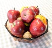Maçãs e fruto vermelhos na cesta acima da tabela Fotos de Stock Royalty Free