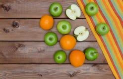 Maçãs e laranjas frescas na tabela de madeira Imagem de Stock Royalty Free