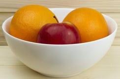 Maçãs e laranjas naturais suculentas frescas em uma placa branca brilhante no fundo de madeira Fotos de Stock