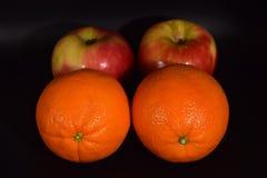 Maçãs e laranjas no preto imagem de stock