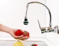 Maçãs e tomates preparados na cozinha. Fotos de Stock
