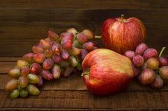 Maçãs e uvas em um fundo rústico de madeira Ainda vida para a ação de graças com frutos do outono Foco seletivo alto Fotos de Stock Royalty Free