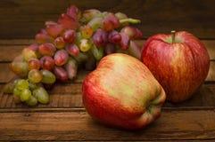 Maçãs e uvas em um fundo rústico de madeira Ainda vida para a ação de graças com frutos do outono Foco seletivo alto Imagens de Stock