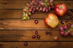 Maçãs e uvas em um fundo rústico de madeira Ainda vida para a ação de graças com frutos do outono Foco seletivo alto Fotos de Stock