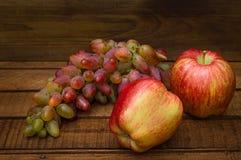 Maçãs e uvas em um fundo rústico de madeira Ainda vida para a ação de graças com frutos do outono Foco seletivo alto Foto de Stock