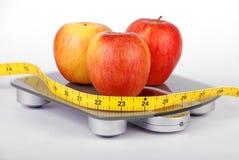 Maçãs em escalas de peso fotografia de stock