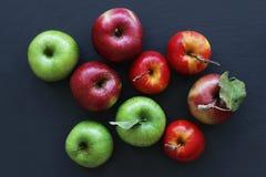 Maçãs em maçãs escuras do fundo, as verdes e as vermelhas fotos de stock royalty free