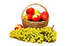 Maçãs em uma cesta e uvas no primeiro plano Fotografia de Stock Royalty Free