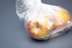 Maçãs frescas dentro de um saco de plástico claro imagem de stock