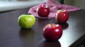 Maçãs frescas na tabela de madeira Maçãs vermelhas e verdes Frutos na tabela filme