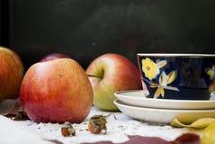Maçãs frescas vermelhas com folhas e copos para o chá Imagens de Stock Royalty Free