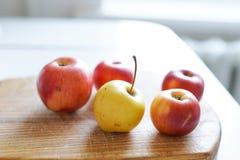 Maçãs frescas vermelhas na placa de madeira velha no fundo claro na cozinha branca Alimento saudável imagens de stock