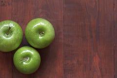 Maçãs maduras verdes em um fundo de madeira Imagens de Stock Royalty Free