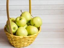 Maçãs maduras verdes em uma cesta amarela de vime Fotos de Stock Royalty Free