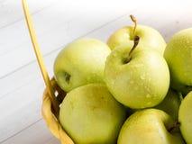 Maçãs maduras verdes em uma cesta amarela de vime Fotos de Stock