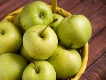 Maçãs maduras verdes em uma cesta amarela de vime Fotografia de Stock