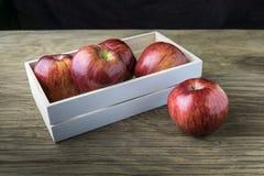 Maçãs na caixa Maçãs vermelhas em uma tabela de madeira Fotografia de Stock