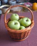 Maçãs na cesta de vime marrom na mesa da cozinha Imagem de Stock Royalty Free