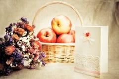 Maçãs na cesta e em flores selvagens Foto de Stock