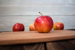 Maçãs na placa de madeira Fotografia de Stock Royalty Free
