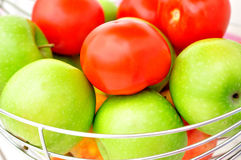 Maçãs verdes e tomates vermelhos. Imagens de Stock