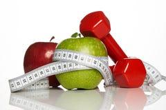 Maçãs verdes e vermelhas com fita de medição e pesos vermelhos Imagem de Stock Royalty Free