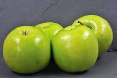 Maçãs verdes em uma placa da ardósia Fotos de Stock Royalty Free