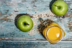 Maçãs verdes frescas e um vidro do suco de laranja fresco imagem de stock