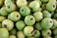 Maçãs verdes frescas no mercado Muitas maçãs um grande contexto para uma loja do fruto Imagens de Stock Royalty Free