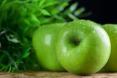 Maçãs verdes maduras com fundo de madeira do dropletson da água Imagens de Stock