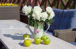 Maçãs verdes maduras e um vaso das peônias em uma tabela de mármore Imagem de Stock