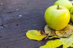 Maçãs verdes maduras em um fundo de madeira com folhas amarelas Fotografia de Stock