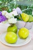Maçãs verdes maduras e um vaso com jacintos em um p Imagens de Stock